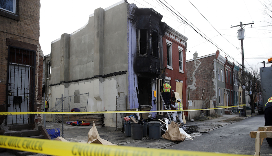 City workers board up the scene of a fatal fire Friday, Jan. 8, 2016, in Philadelphia. A pregnant mother ran into her burning row house to rescue her toddler Friday morning but died along with the child when smoke prevented their escape, officials said. (AP Photo/Matt Rourke)