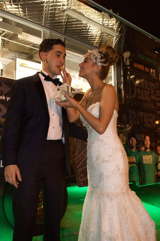 Marissa Patterson and Justin Fiordimondo snack on treats from the Wahlburgers truck at their VIE wedding this past fall. Photo by Sarah Christiansen.