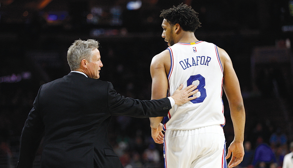 Coach Brett Brown talks mid-game with star center Jahlil Okafor. Photo courtesy of the Associated Press.