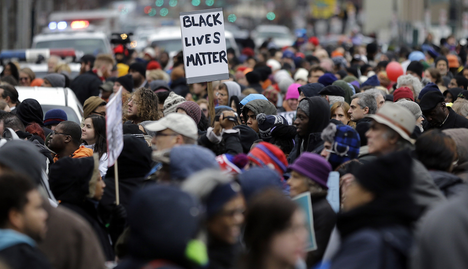 """A large crowd marches to mark the holiday honoring the Rev. Martin Luther King Jr., Monday, Jan. 19, 2015, in Philadelphia, Pa. Participants called for a higher minimum wage, an end to police """"stop and frisk"""" tactics and a locally controlled school system. (AP Photo/Mel Evans)"""