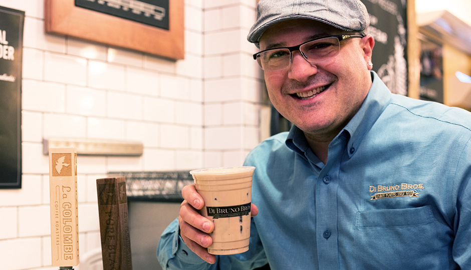 Di Bruno Bros. Emilio Mignucci with a cup of La Colombe Draft Latte.