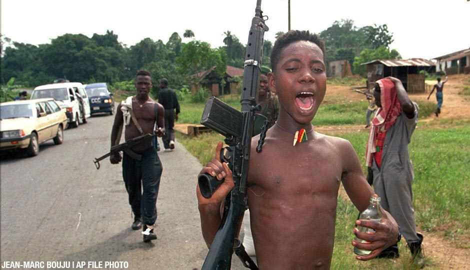 In this AP file photo, an intoxicated young rebel with the United Liberation Movement of Liberia (ULIMO), shouts while walking along the highway leading to Tubmanburg, 40 miles northwest of the capital Monrovia, Tuesday January 9, 1996.