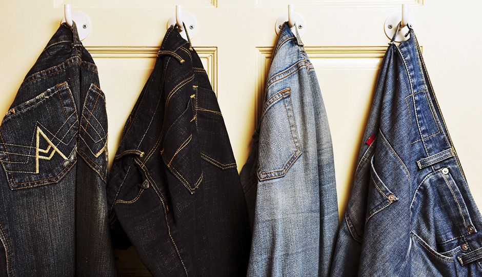 Several jeans with different shades of blue hung on the door