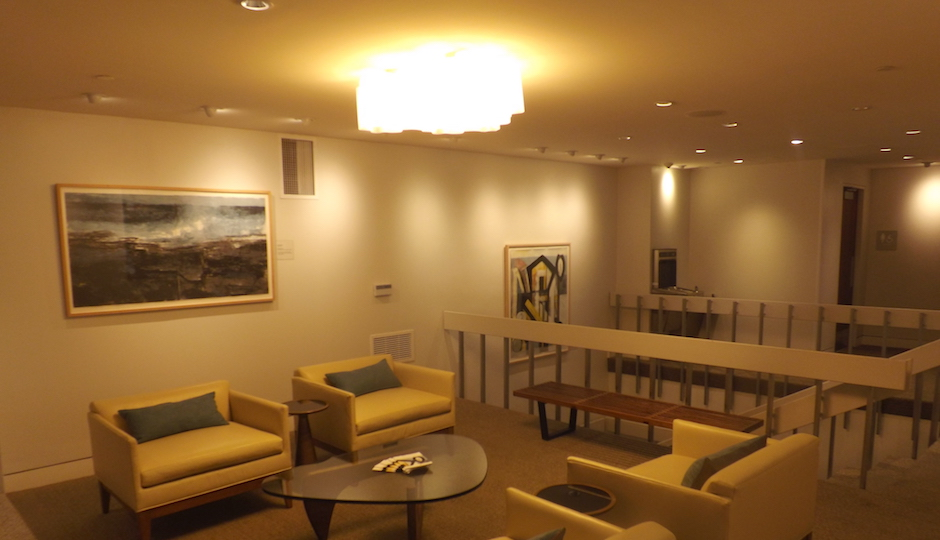 This lounge near the Towne Center concierge desk is the closest in appearance to the way the entire community center looked before the renovation; the staircase at right was the original and only access to the lower-level shops, parking garage and pool. Even this space now serves as an art showcase after the renovation project, which sprinkles works by Philadelphia artists throughout the development's public areas. | Photos: Sandy Smith