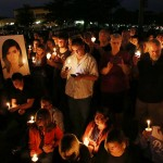 People stand near a large photograph as they hold candles during a vigil to honor Christina Grimmie, the 22-year-old singer who was fatally shot Friday night after a concert in Florida, Monday, June 13, 2016, in Evesham Township, N.J.