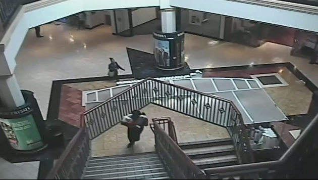 A woman identified as 32-year-old Cherie Amoore walks through and out of the King of Prussia mall with seven-month-old