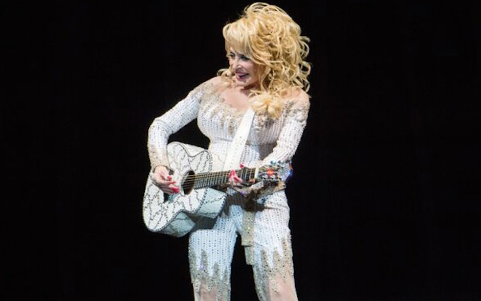 Dolly Parton strums her guitar on stage at the Mann Center in ...