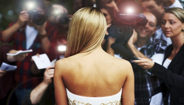 Rear-view of a young starlet caught in the flashes of paparazzi cameras and the screams of adoring fans