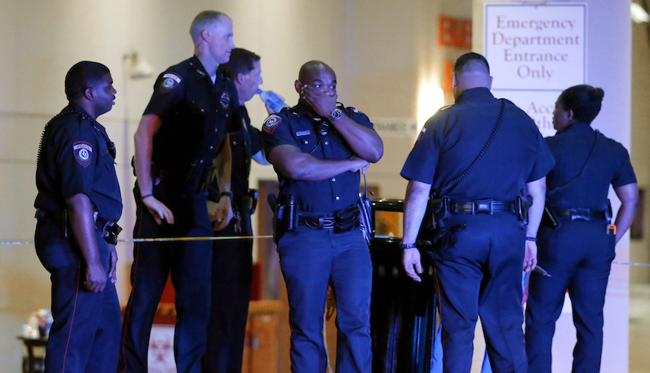 A Dallas police officer covers his face as he stands with others outside the emergency room at Baylor University Medical Center, Friday, July 8, 2016, in Dallas. (AP Photo/Tony Gutierrez)