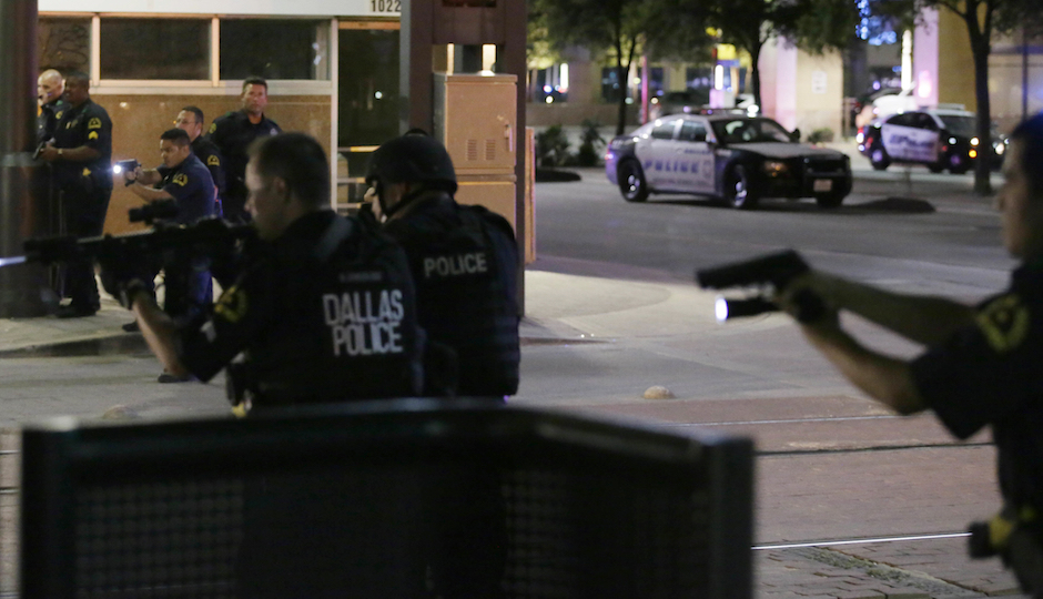 Dallas police move to detain a driver after a shooting in downtown Dallas, Thursday, July 7, 2016. (AP Photo/LM Otero)
