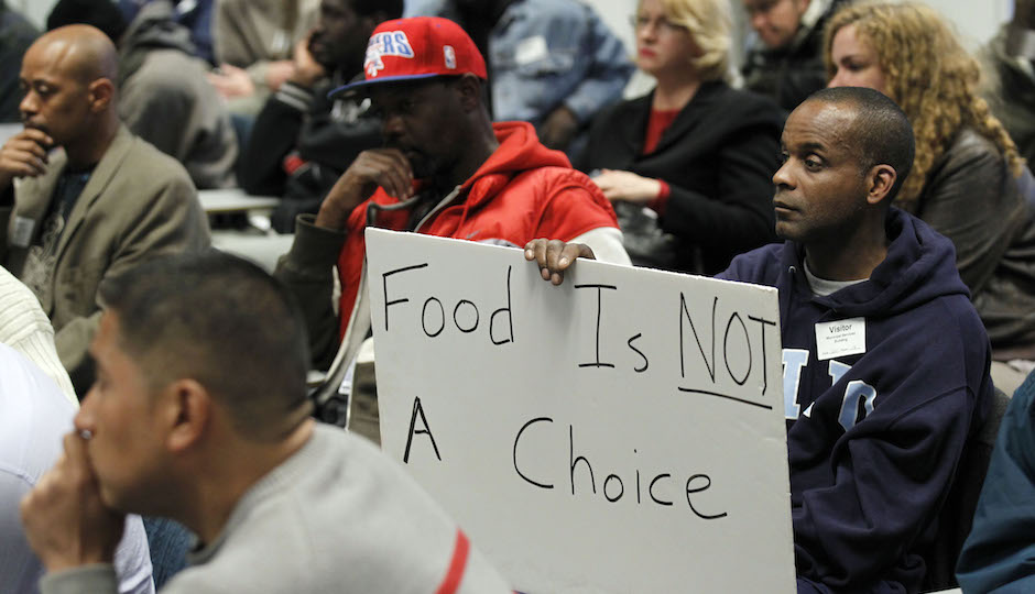 A man holds a sign during a Philadelphia Department of Public Health hearing in reference to regulations banning outdoor food distribution Thursday, March 15, 2012 in Philadelphia. (AP Photo/Alex Brandon)
