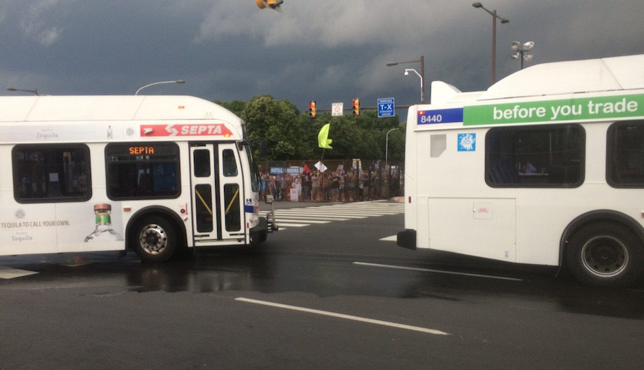 SEPTA shuttle buses, fresh from dropping off passengers, round the intersection of Broad Street and Pattison Avenue as supporters of Sen. Bernie Sanders stage a protest outside the convention security perimeter. | Photos: Sandy Smith