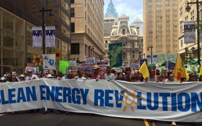 Protesters march holding a 'Clean Energy Revolution' sign