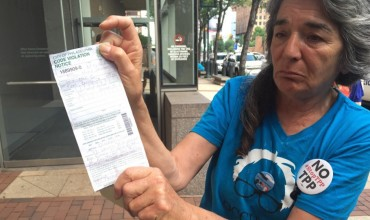 Anna Marie Sternberg displays her code violation citation in front of the federal courthouse in Philadelphia. (Photo by Brian Thomas)