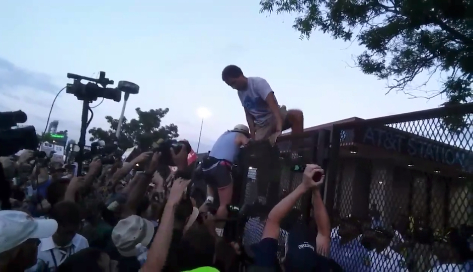 Protesters scale the DNC security fence on Tuesday, July 26th. (Photo via screenshot of video from Twitter user @rousseau_ist)