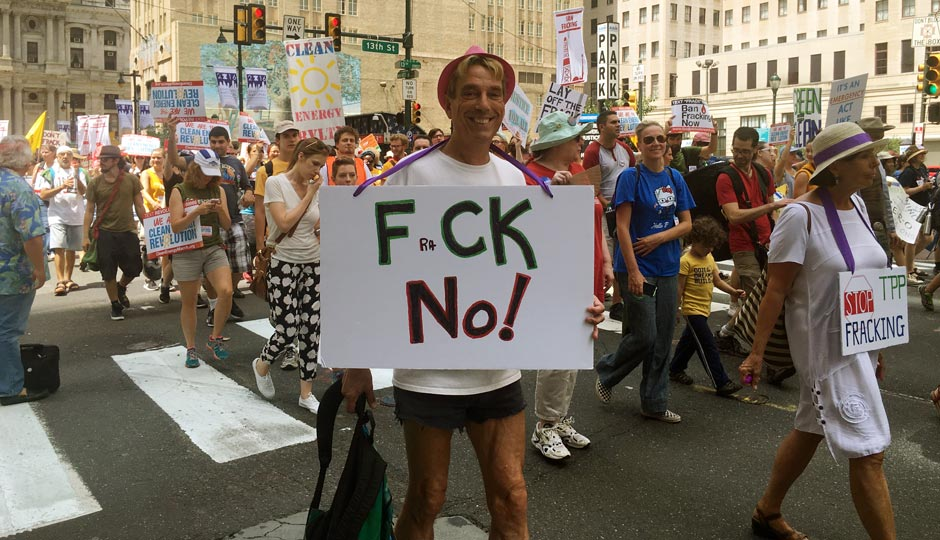 A man holds a FraCK NO! sign while walking on Market Street during an environmental protest