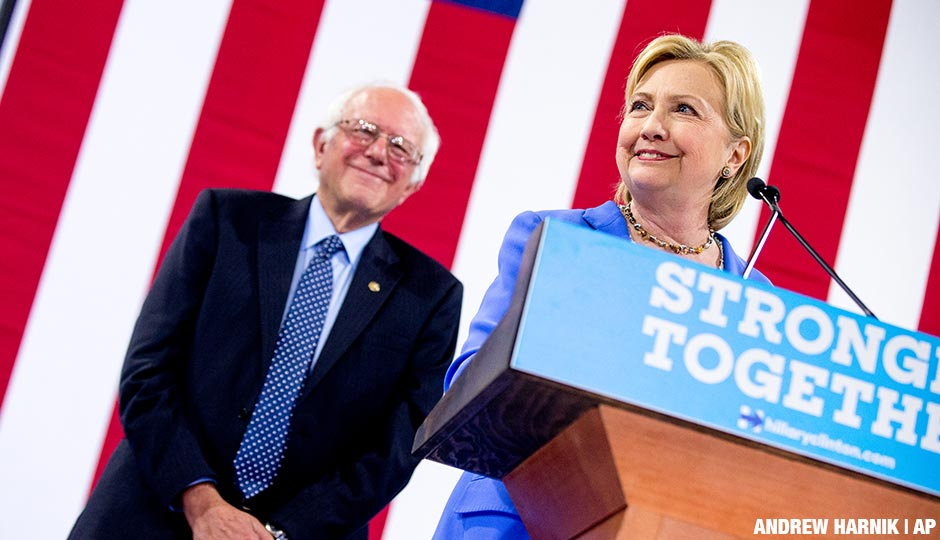 Hillary Clinton accompanied by Sen. Bernie Sanders, left, smiles while speaking as Sanders endorses Clinton at a rally at Portsmouth High School in Portsmouth, N.H., Tuesday, July 12, 2016.