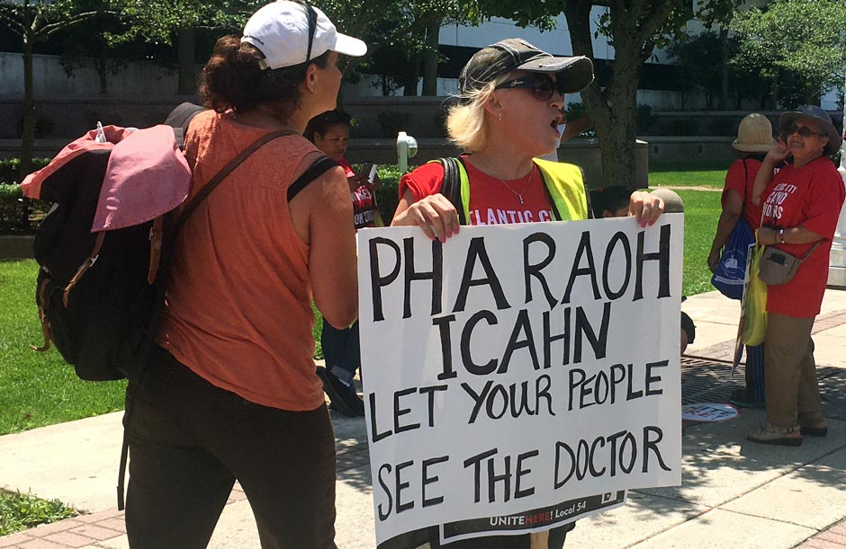 A striking union worker outside the Trump Taj Mahal in Atlantic City holds a sign that reads 'Pharaoh Icahn: Let your people see the doctor.'