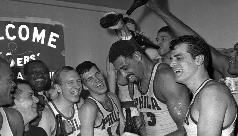 Wilt Chamberlain of the Philadelphia 76ers gets champagne poured on him on April 12, 1967, in the 76ers dressing room after Philadelphia defeated the Boston Celtics 140-116 to win the Eastern Division NBA championship. Surrounding Chamberlain are from the left are Bob Weiss, Matt Guokas, Wally Jones and Dave Gambee. AP Photo