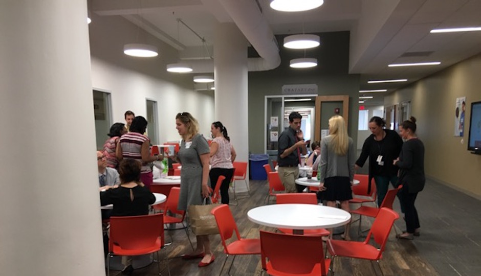 """Three central common spaces form the """"hub"""" of the """"neighborhood"""" where EPIC@Jeff employees work. The cafe space hosts a wide range of activities, not all of them related to eating.