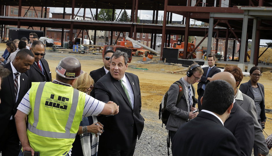 FILE In this Wednesday, Sept. 24, 2014 file photograph, Gov. Chris Christie, center, greets a worker at the construction of a huge new KIPP Cooper Norcross Academy school in Camden, N.J. Christie has made frequent stops in the high-crime city, stressing his efforts working with local Democratic lawmakers, including Mayor Dana Redd. Under his watch, there have been major changes to schools, policing and efforts to attract businesses. (AP Photo/Mel Evans,file)