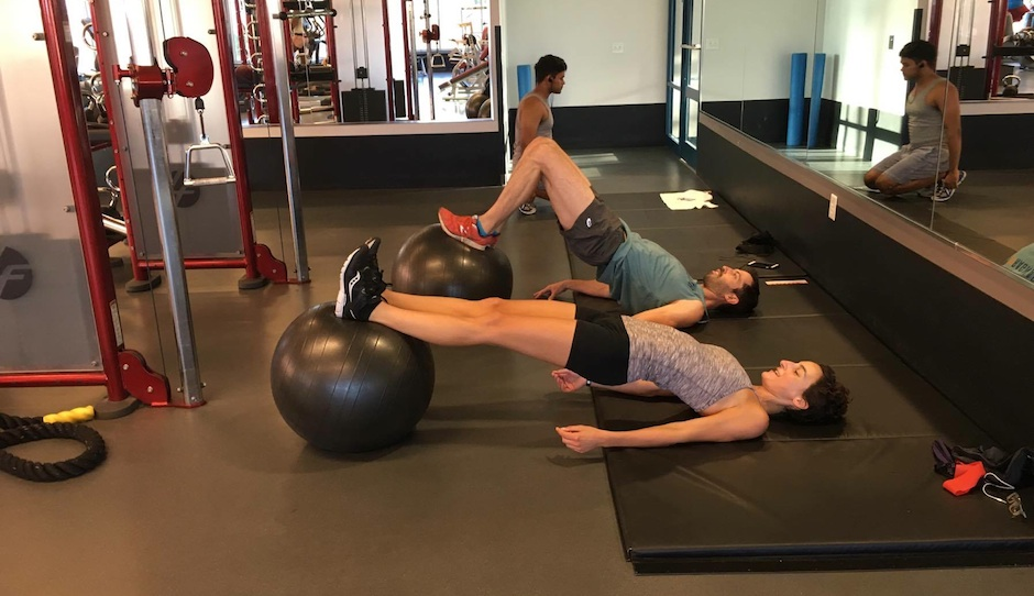 Workout testers Alon and Emma doing hamstring curls.