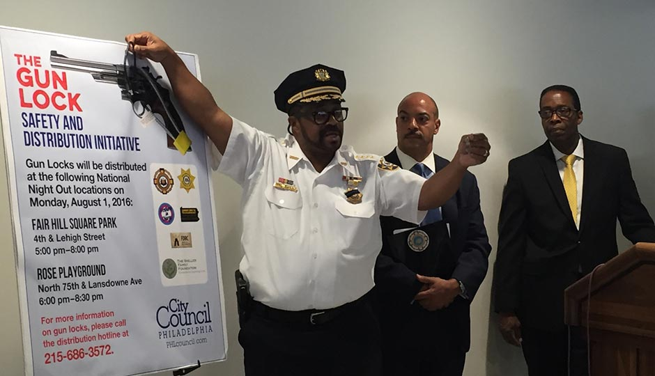 Sheriff Jewell Williams (left) demonstrates how to use a gun lock while District Attorney Seth Williams (center) and City Council President Darrell Clarke (look on).