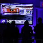 Supporters gather around the monitor to check the early election results during Republican presidential candidate Donald Trump's election night rally, Tuesday, Nov. 8, 2016, in New York. (AP Photo/John Locher)