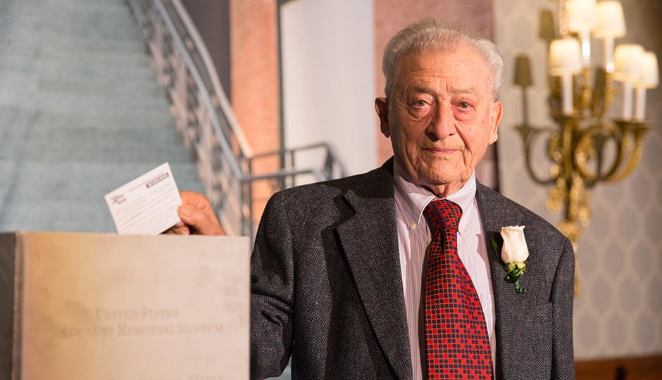 """George Sakheim, a Philadelphia-area Holocaust survivor, places a message into a time capsule at the U.S. Holocaust Memorial Museum's """"What You Do Matters"""" dinner on Wednesday evening. Photo courtesy of the United States Holocaust Memorial Museum"""