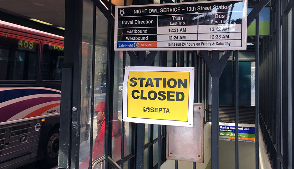 'Station Closed' sign at SEPTA El stop, man smoking in background