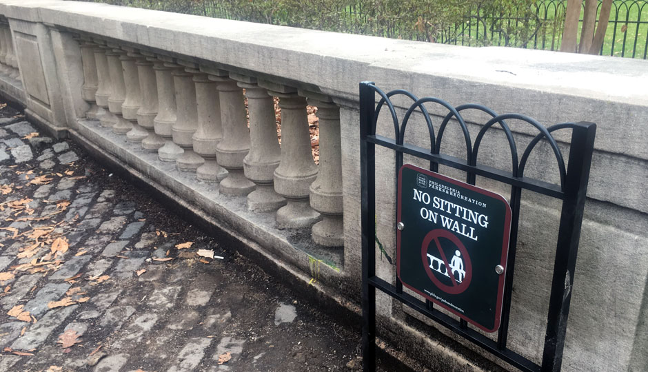 "A sign says ""no sitting on wall"" in Rittenhouse Square"
