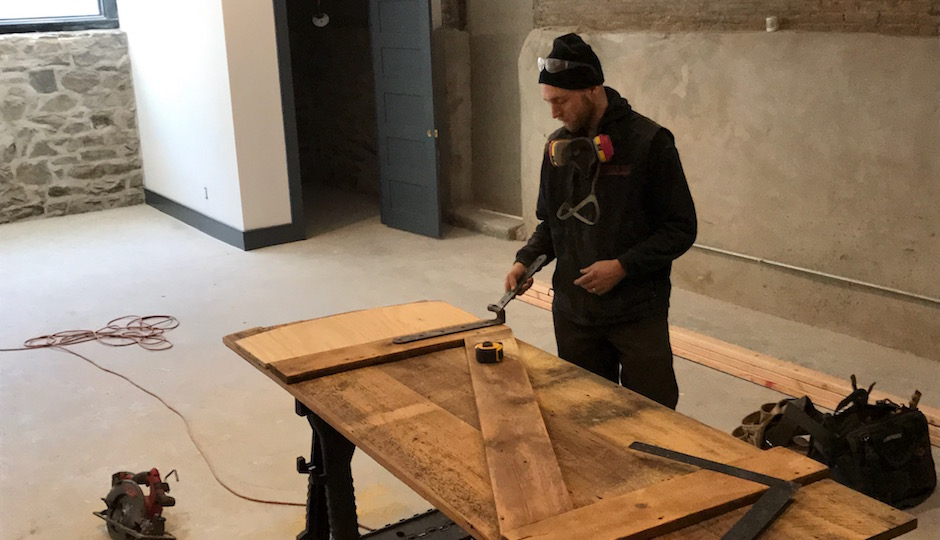 Made by hand, not beforehand: A Red Oak construction crew member works on the hinge of a custom door made from wood salvaged from the demolition of the parish house's interior. The door will lead from this home's finished basement rec room to the mechanical room. | Photos: Sandy Smith