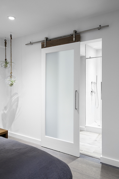 A sliding translucent glass door makes the bathroom brighter by letting in natural light.