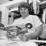 Phillies first baseman Pete Rose looks over a children's book by teammate Tug McGraw as he sits in the club's locker room at Jack Russell Stadium in Clearwater, Florida. (AP Photo/Ray Stubblebine)