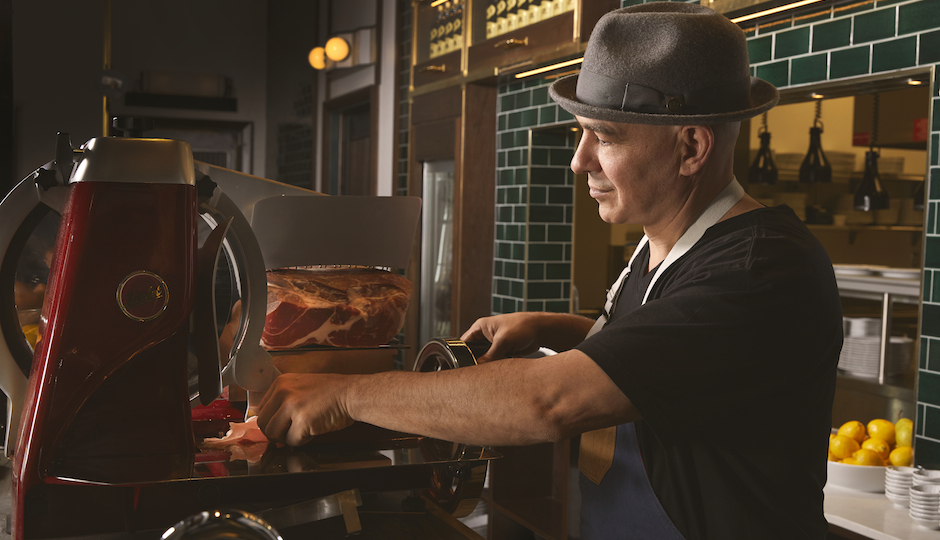 Wearing his signature hat, Michael Symon works the slicer at Angeline at the Borgata. (Photo by Michael Persico)
